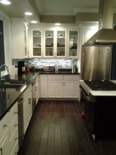 Cupboards painted white, black granite, glass back splash, walnut hardwoods, black walnut island cupboards with with marble counter top - Remodel by Elegant Solutions