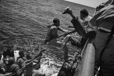Francesco Zizola - 2016 Photo Contest | World Press Photo_Migrants climb on board of a rescue ship by Doctors without Borders to escape their sinking rubber dinghy.