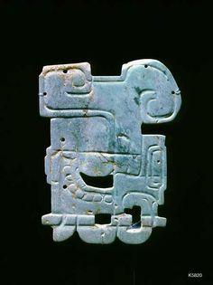 Maya. jade. height 5.0 cm. Appliqué in form of deity face. note tiny holes for attaching.