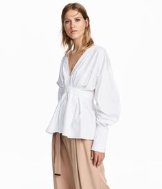 White. Blouse in thick, woven cotton fabric with a low-cut V-neck and heavily dropped shoulders. Pleats and wide elasticized seam at waist. Long, wide
