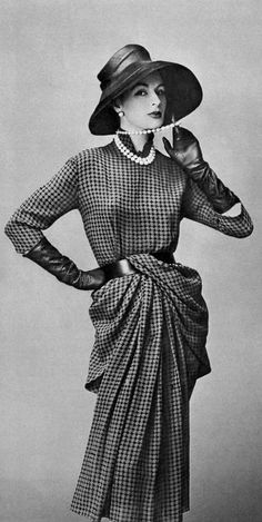Model in chiffon hazelnut and black houndstooth dress, hips are draped and one long panel slides under the belt, by Catherine Sauve, photo by Georges Saad, 1957