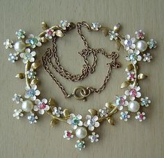 This elegant necklace has a daisy design bib adorned with lustrous faux pearls and tiny shimmering multi-coloured aurora borealis faceted glass stones. The stones mounted in articulated metal settings with a white enamel and goldtone finish.