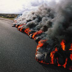 Kilauea volcano on Hawaii, lava from volcano that has been erupting since 1983. A lava flow taking over a highway and burning the asphalt. This lave is so hot it melts and burns the asphalt, creating thick clouds of black  smoke.