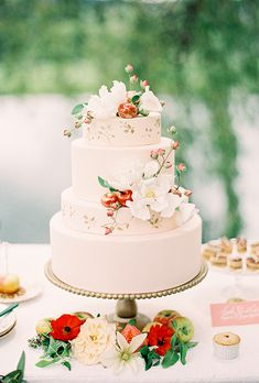 Brides.com: 23 Cakes We Love for Summer Weddings A four-tiered white wedding cake with blue-and-gold details created by Sweet Elizabeth Cakes.Photo: Tasha Rae Photography