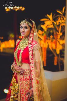 Bridal Portrait - Red Bridal Lehenga with Gold Jewelry and Gold Kaleere | WedMeGood #wedmegood #indianbride #indianwedding #red #bridal #portrait
