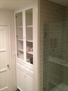 White bathroom linen closet with hamper. Plenty of shelves for storage and hamper on bottom.