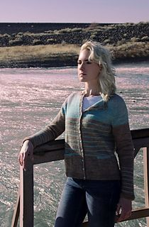 A simple women's cardigan with a boxy fit is worked from the bottom hem up in one piece. It features afterthought pockets, and a rounded crew neckline. The body of the sweater is worked in color-blocked stockinette and narrow stripes. The sweater body is knit back and forth from the bottom hem upward. The sleeves are knit in the round from the cuffs to the underarms, and then joined to the body, which is then shaped with raglan sleeves up to the neckline. The neckband and front button bands…