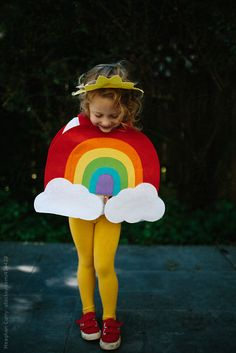 little girl dressed up in a rainbow halloween costume