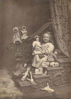 Little girl and her doll collection... I love that one on the floor that's missing it's head. lol!