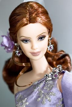 This redheaded version of Barbie® 2003 was limited to 2500 dolls worldwide. She wears a lavender gown that goes over one shoulder to create an elegant look. The bodice of the gown has shiny, silvery caviar beading. She also wears a dark lavender organza floor length wrap trimmed at the bottom with taffeta. Her hair is pulled back into an elegant low ponytail that is curled on the bottom. 120.00+