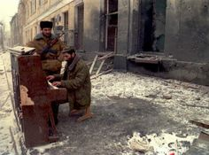 A Chechen soldier plays piano in one of the main streets of Grozny, where Russian jets had conducted bomb attacks over several days [27 December 1994]