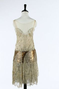 One Item | Kerry Taylor Auctions A Callot Soeurs couture ivory tulle and bronze lame flapper dress, Summer, 1927. the matching oyster pink satin slip with printed gold on ivory silk label 'Callot Soeurs, Paris, Ete 1927, Nouvelle Marque Deposee and indistinctly numbered '96199', the bodice adorned with silver and opalescent sequins, fine gold strip areas to the ground,  - See more at: http://kerrytaylorauctions.com/one-item/?id=48auctionid=401#sthash.jhW56mES.dpuf