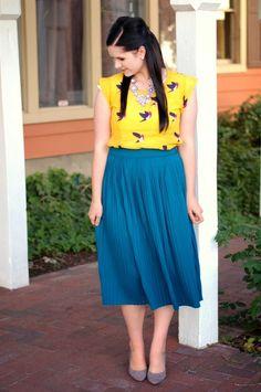 Teal pleated skirt, yellow bird shirt, gray heels