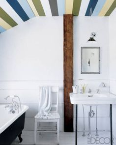 In the upstairs bath of a New York home, the tub has fittings from George Taylor Specialties, the hanging light is from Paula Rubenstein, and homeowner Malene Waldron designed and painted the ceiling.   - ELLEDecor.com