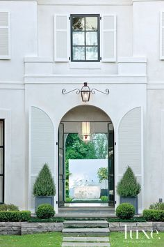 The large scale of the home's elegant arched entryway provides a dramatic first impression of luxury and  space. The view through the glass ...