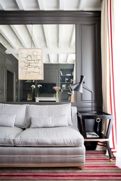 michele bönan's new hotel, charcoal gray interior with red striped rug, dove gray sofa, neutral gray, stone gray, pantone harbor mist