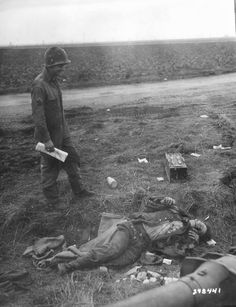 A smiling US Army Corporal William R. Kamp observes a German dead near the town of Frauwüllesheim, Feb 28, 1945.