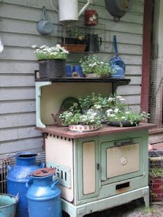 Old stove as a potting table- planting containers are vintage pots and pans
