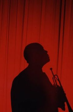 Silhouette of American jazz musician Louis Armstrong as he holds his trumpet Atlantic City New Jersey 1965