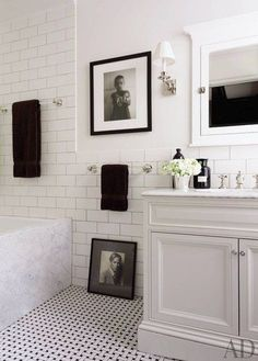 The tiles in accessories designer Richard Lambertson's bath are by Nemo Tile Co., and the towels are by Restoration Hardware; the art includes a photograph by Machiel Botman, at top, and a Guzman portrait of Lumberton | archdigest.com