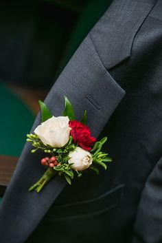 Winter wedding groom boutonniere of blush majolica spray roses, burgundy mini carnations, pepperberry by www.redpoppyfloral.com