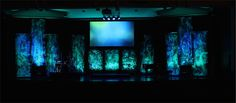 Kaleb Wilcox at Topeka Bible Church in Topeka, Kansas brings us their unique take on the Texturesized design. Instead of brooming on the white paint, they splashed the paint onto the landscape fabric. This made it look more like bubbling sea foam – a wave splashing over the stage. They bought a 4'x100' role of black landscape fabric, cut it to the needed lengths, then used brooms to randomly splatter flat white paint on them. Then they attached 4' long 1