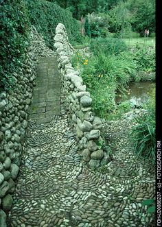 Mosaic pebble paving on stone bridge with pebble walls in large country garden