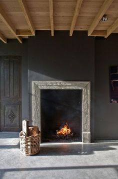 Gray wall & rustic framed fireplace.