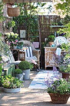 Country Garden Retreat...rustic twiggy fence & baskets...chippy wicker & metal pots...with flowers...sit a spell.