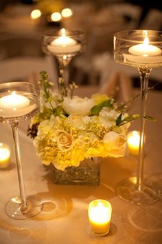 centerpiece candles out around the black vase with the yellow flowers