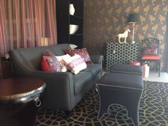 dark lounge and furnishings with colourful cushions and hint of colour in stripes of the sheer curtain behind lounge