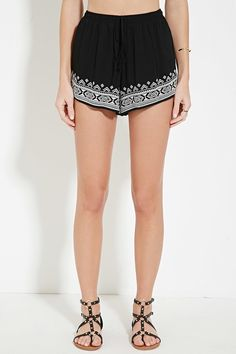 A pair of knit shorts with geo embroidery along the front hem and an elasticized drawstring waist.