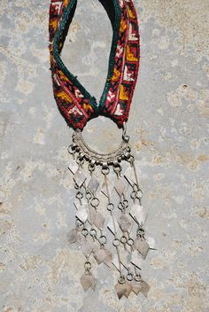 Kinship Stories: Tribal art necklace whose base is made of vintage Turkoman embroidery. It comes from an old Afghani male hat. The dangling earring is vintage Yemeni. It is made of mixed silver (50k). This piece is entirely handmade and is one of a kind.