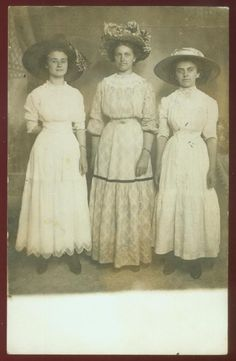 These three women friends must have had their photo taken at a summer fair. They have very tiny waists and very large hats!