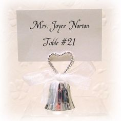 """Silver Double Heart Rope Bell Placecard Holder (Set of 12)   Nuptial Knick Knacks    Made of Silver Plate and comes with removable White Satin Ribbon.  Measures Approx: 1 1/4"""" x 2 3/8""""    Sold in Sets of 12    Yes, The Bell Does Ring!    Placecard is held between the 2 Rope Design Hearts."""
