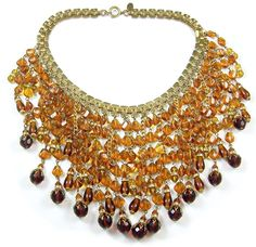 Spectacular 1950's MIRIAM HASKELL amber and topaz glass bead pendants bib necklace. Features 44 various length pendants comprised of amber glass beads, each finished with either a faceted round or an elongated cylindrical teardrop topaz glass bead. The faceted round beads have ornate gilt and clear crystal rondelle findings.
