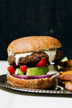 The best healthy vegan black bean burgers are gluten free, packed with veggies and filled with plenty of spices. This is the ultimate vegan black bean burger recipe that's easy to make, holds together well and is incredibly delicious! Top with avocado, onion, tomato and a super addicting garlic tahini sauce. #veganrecipe #blackbeans #burgers #veganburger #glutenfree #mealprep #dinner #dairyfree...