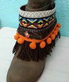 Cubre botas realizado en tonos naranjas y marrones, con pasamanería, flecos y adornos diversos.