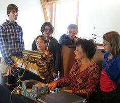 Children gather at the piano with Bernadette Aubin Allan