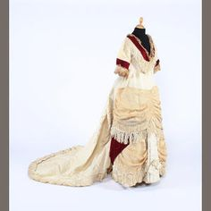 early 1870s high waisted and bustled dress of cream ribbed silk, with a deep V neck, decorated with burgundy silk plush and gathered flounces of cream gauze trimmed with silk fringing