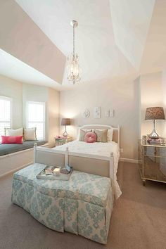 Feminine Bedroom with chandelier, upholstered headboard, & antiqued mirrored furniture.
