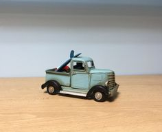 Vintage light blue surf truck miniature with surfboard and life vest on it