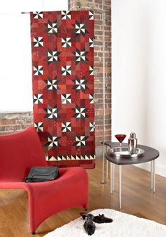 Quilt displayed on a telescoping rod, which uses tension to balance between floor and ceiling. Besides spicing up a so-so corner in your home, consider three rods placed side by side to create an artful room divider.