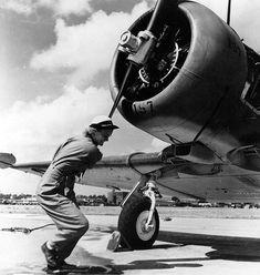WAVES Aviation Machinist's Mate 3rd Class Violet Falkum turning the Pratt & Whitney R-1340 radial engine of a SNJ-4 training plane Naval Air Station Jacksonville Florida United States 30 November 1943.