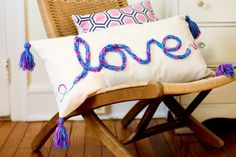 "DIY finger kint, tasseled pillow. This cute ""love"" pillow would make a wonderful Valentine's Day gift or wedding shower gift. Or finger knit a name or any word in any color your heart desires. How to finger knit and instructions for making the pillow, forming and stitching the word ""love"" onto the fabric and creating the tassels."