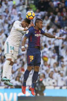 """Real Madrid's Brazilian midfielder Casemiro (L) and Barcelona's Brazilian midfielder Paulinho jump for the ball during the Spanish League """"Clasico"""" football match Real Madrid CF vs FC Barcelona at the Santiago Bernabeu stadium in Madrid on December 23, 2017.  / AFP PHOTO / CURTO DE LA TORRE"""