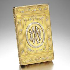 THE 25TH WEDDING ANNIVERSARY: A FABERGÉ IMPERIAL JEWELLED FOUR-COLOUR GOLD CIGARETTE CASE, WORKMASTER AUGUST HOLMSTRÖM, ST PETERSBURG, 1899 in neoclassical taste, the surface richly chased with flowers within arches and Ionic columns, the base applied with diamond-set Roman numeral XXV, reversible to form the Latin initials M and V for Grand Duchess Maria Pavlovna and Grand Duke Vladimir Alexandrovich in commemoration of their 25th wedding anniversary