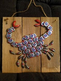 Bottle cap art, crab Approximately 12 x 12 inch wood with bottle cap crab. Beer cap brands may vary. Bottle Top Crafts, Bottle Cap Projects, Diy Bottle, Beer Cap Crafts, Wine Cork Crafts, Recycled Crafts, Diy And Crafts, Arts And Crafts, Bottle Cap Art