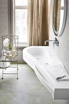 Choć tę łazienkę zdobi beton na ścianach i podłodze oraz designerska umywalka, nie jest ona na wskroś nowoczesna. Postawiono w niej na subtelny eklektyzm. Kute ogrodowe krzesło, haftowany ręcznik i starodawny dzban wywołują romantyczne skojarzenia.