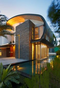 This waterfront home in Singapore is enclosed by a curvaceous roof